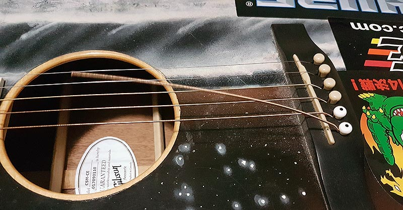Remove string from guitar bridge